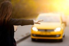 De donkerbruine taxi van het gebaarvangsten van de vrouwenhand op de weg Royalty-vrije Stock Foto's