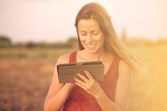 De donkerbruine toegepaste tablet warme filter van de vrouwenlezing Royalty-vrije Stock Foto
