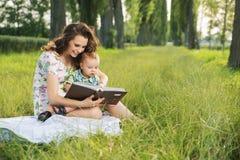 De donkerbruine verhalen van de moederlezing voor haar kind Stock Afbeelding