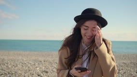 De donkerbruine vrouw babbelt door sms door smartphone op zandig strand in de lente stock videobeelden