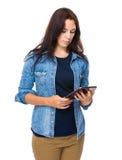 De donkerbruine vrouw bekijkt tablet Royalty-vrije Stock Fotografie