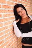 De donkerbruine vrouw bevindt zich dichtbij bakstenen muur Stock Foto's