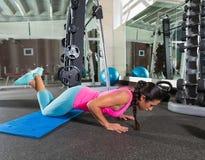 De donkerbruine vrouw bij gymnastiekknieën verhoogt opdrukoefening Stock Foto