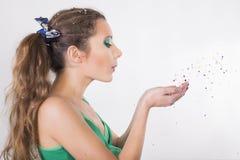 De donkerbruine Vrouw blaast de confettien op haar Verjaardagspartij weg Stock Foto's