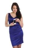 De donkerbruine vrouw in blauwe kleding toont uw telefoon Stock Fotografie