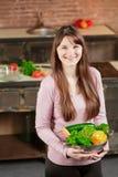 De donkerbruine vrouw in de keuken houdt een kom met verse groenten en bekijkt de camera en glimlacht Gezond voedsel Stock Afbeeldingen