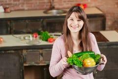 De donkerbruine vrouw in de keuken houdt een kom met verse groenten en bekijkt de camera en glimlacht Gezond voedsel Stock Fotografie