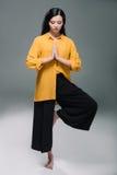De donkerbruine vrouw die met gesloten ogen yoga in boom uitoefenen stelt, Stock Fotografie