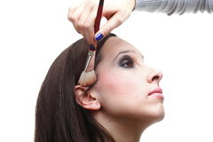 De donkerbruine vrouw die van Beauti poeder met borstel toepast Stock Foto