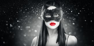 De donkerbruine vrouw die van de schoonheidsglamour Carnaval-veer donker masker, partij over vakantie zwarte achtergrond dragen stock foto