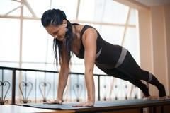 De donkerbruine vrouw in een donkere jumpsuit die zich in Duw UPS, persups oefening, phalankasana, Plank bevinden stelt voor grot Royalty-vrije Stock Afbeeldingen