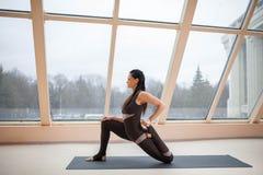 De donkerbruine vrouw in een donkere jumpsuit die zich in de oefening van de Paardruiter, anjaneyasana bevinden stelt voor grote  Royalty-vrije Stock Foto