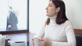 De donkerbruine vrouw in een koffie drinkt een drank stock video