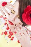 De donkerbruine vrouw in gele en rode kleding met papaverbloem in haar haar, papaverring en creatieve spijkers, sloot ogen Stock Foto's