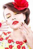 De donkerbruine vrouw in gele en rode kleding met papaverbloem in haar haar, papaverring en creatieve spijkers, sloot ogen Royalty-vrije Stock Foto's
