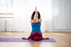 De donkerbruine vrouw het praktizeren adelaar stelt in yogaklasse Royalty-vrije Stock Fotografie