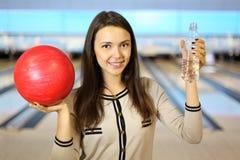 De donkerbruine vrouw houdt bal en fles in kegelen Royalty-vrije Stock Fotografie