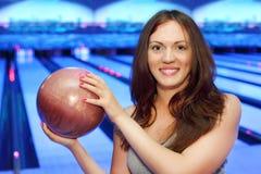 De donkerbruine vrouw houdt bal en glimlacht in kegelen Royalty-vrije Stock Foto's