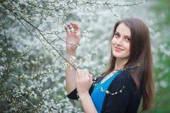De donkerbruine vrouw inhaleert de geur van bloemen Royalty-vrije Stock Afbeeldingen