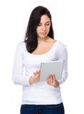 De donkerbruine vrouw las de digitale tablet Royalty-vrije Stock Afbeeldingen