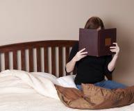 De donkerbruine Vrouw leest in Bed Stock Afbeeldingen