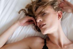 De donkerbruine vrouw ligt op bed met gesloten ogen Royalty-vrije Stock Afbeelding