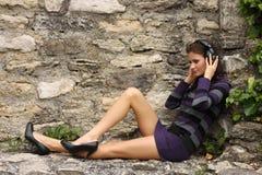 De donkerbruine vrouw luistert aan muziek Stock Foto