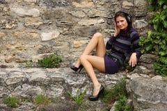 De donkerbruine vrouw luistert aan muziek op een rots Royalty-vrije Stock Fotografie