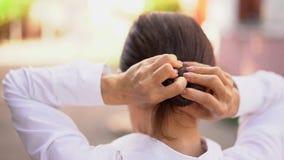 De donkerbruine vrouw maakt een haarknotje op haar hoofd stock footage