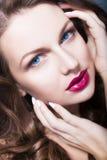 De donkerbruine vrouw met blauwe ogen zonder maakt omhoog, natuurlijke onberispelijke huid en handen dichtbij haar gezicht Royalty-vrije Stock Foto's