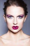 De donkerbruine vrouw met creatief maakt omhoog tot violette oogschaduwwen volledige rode lippen, blauwe ogen en krullend haar me Royalty-vrije Stock Fotografie