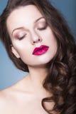De donkerbruine vrouw met creatief maakt omhoog tot violette oogschaduwwen volledige rode lippen, blauwe ogen en krullend haar me Stock Foto