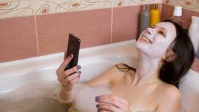 De donkerbruine vrouw met een masker op haar gezicht ligt in badkamers en chattin door mobiele telefoon en te lachen stock footage