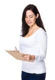De donkerbruine vrouw neemt nota over klembord Stock Foto's