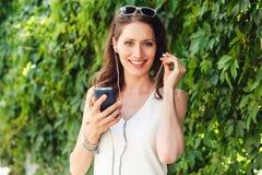 De donkerbruine vrouw neemt oortelefoon in haar oor en holdingstelefoon op Royalty-vrije Stock Afbeeldingen