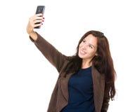 De donkerbruine vrouw neemt selfie met slimme telefoon Stock Foto's