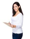 De donkerbruine vrouw schrijft op klembord Stock Foto
