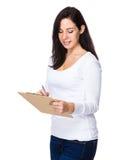 De donkerbruine vrouw schrijft op klembord Stock Afbeeldingen