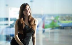 De donkerbruine vrouw spreekt op mobiele telefoon in de luchthaven Royalty-vrije Stock Afbeeldingen