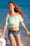 De donkerbruine vrouw stelt overzees in jeansborrels in werking Stock Fotografie