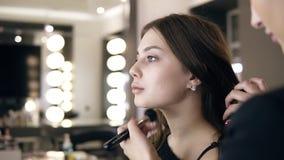 De donkerbruine vrouw stichting of toner op het gezicht van het model toepassen en de hals die met een groot zwarte maken omhoog  stock videobeelden