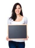 De donkerbruine vrouw toont met bord Stock Afbeeldingen