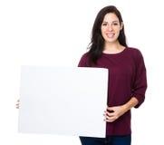 De donkerbruine vrouw toont met witte raad Stock Fotografie