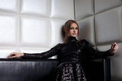 De donkerbruine vrouw van de schoonheid op bank in nachtclub royalty-vrije stock fotografie