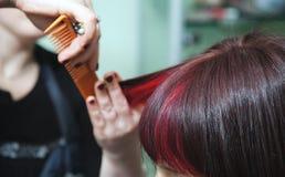 De donkerbruine vrouw van kappersscharen met rode haarbundels Royalty-vrije Stock Foto's