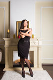 De donkerbruine vrouw van schoonheidsyong dichtbij open haard thuis stock afbeelding