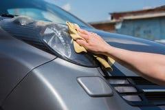 De donkerbruine vrouw wast haar auto Stock Foto's