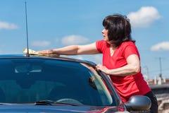 De donkerbruine vrouw wast haar auto Stock Afbeelding
