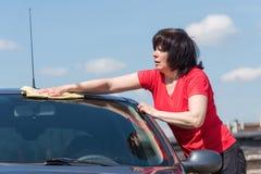 De donkerbruine vrouw wast haar auto Stock Afbeeldingen