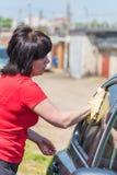 De donkerbruine vrouw wast haar auto Royalty-vrije Stock Afbeeldingen